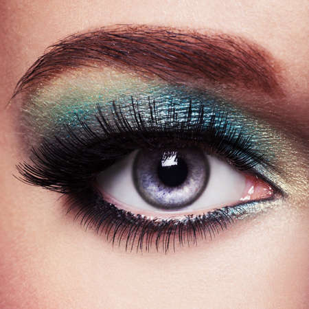 motton blue: Womans eye with green eye make-up. Long eyelashes