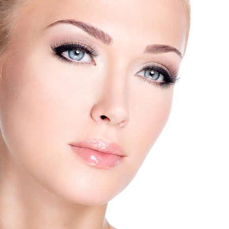 Nahaufnahmeportrait der jungen schönen Frau, weiß mit den langen falschen Wimpern über weißem Hintergrund