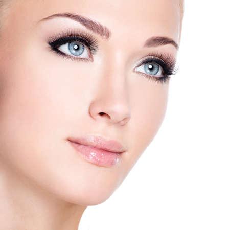 Primer retrato de la joven y bella mujer blanca con largas pestañas falsas sobre el fondo blanco