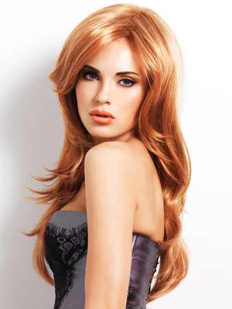 Schöne Frau mit langen geraden roten Haaren. Mode-Modell auf weißem Hintergrund