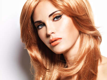glamour makeup: Closeup portrait  of a beautiful woman with long straight red hair and glamour makeup . Fashion model over white background