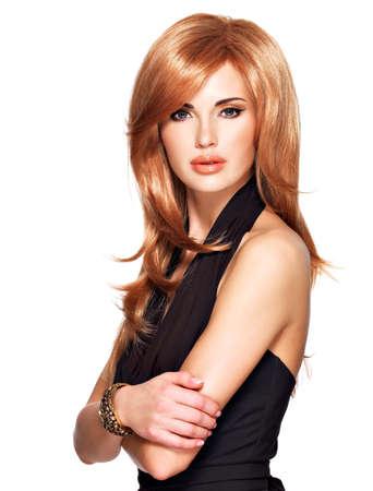 capelli lunghi: Bella donna con i capelli dritti lungo rossi in un abito nero. Modella in posa nello studio. Isolati su bianco Archivio Fotografico