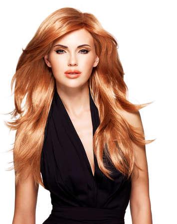 Mooie vrouw met lange rechte rood haar in een zwarte jurk. Fashion model poseren in studio. Geïsoleerd op wit