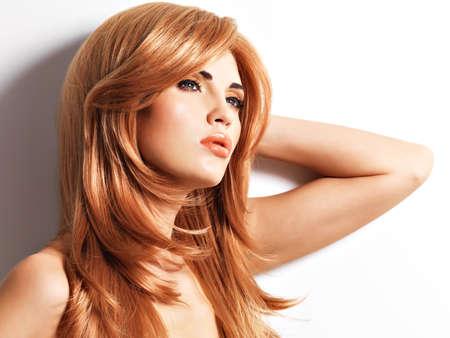 mujer bonita: Mujer hermosa con el pelo largo roja directa. Modelo de moda sobre fondo blanco Foto de archivo