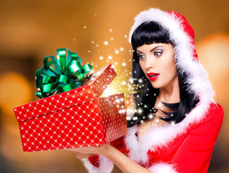 woman surprise: Photo of the surprised  snow maiden looks into the christmas box  with gift in it -  over creative background Stock Photo