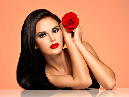 glamour girl: Portrait of  the pretty  beautiful woman with  bright fashion makeup holds red rose. Attractive model posing at studio Stock Photo