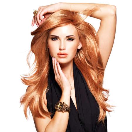 capelli lunghi: Bella donna con lunghi capelli rossi dritti in un abito nero di toccare il viso. Modella in posa nello studio. Isolati su bianco