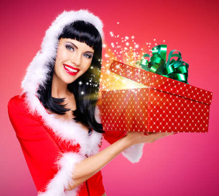 Photo of surprised snow maiden with a christmas gift with magic shining from box - studio red background