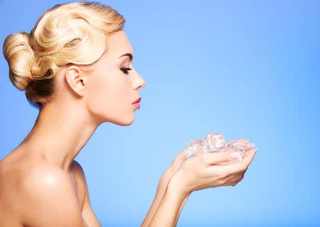 Perfil de la mujer hermosa joven con hielo en sus manos sobre fondo azul. Foto de archivo