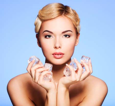 cubo: Hermosa mujer joven con hielo en sus manos sobre un fondo azul.