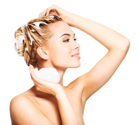 Porträt einer lächelnden jungen Frau, die ihr Haar auf einem weißen Hintergrund Standard-Bild