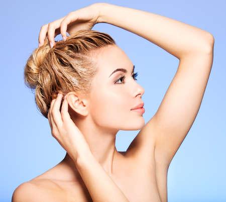 Portret van een jonge vrouw het wassen van haar haar op een blauwe achtergrond