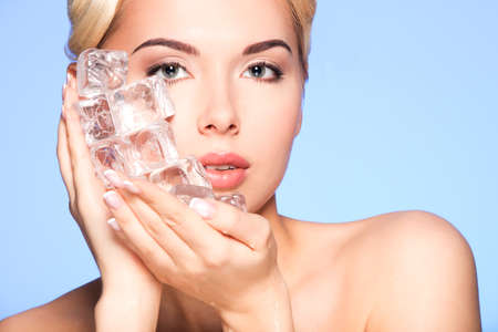 cubes: Closeup portrait of beautiful young woman applies the ice to face on a blue background. Stock Photo