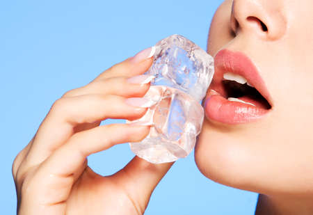 Closeup portrait of beautiful young woman applies the ice to face on a blue background. Stockfoto