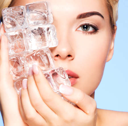 Closeup portrait of beautiful young woman applies the ice to face on a blue background. Banque d'images