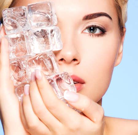 cubo: Primer retrato de mujer joven y bella se aplica el hielo a cara en un fondo azul.