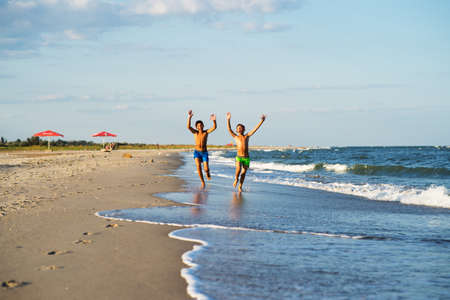 raised arms: Two happy boys running on the sea beach at summer with raised arms Stock Photo