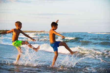 Due ragazzi adolescenza giocare in acqua di mare spruzzi d'acqua i piedi