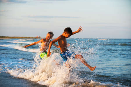 family activities: Two boys adolescence playing in the sea water splashing feet water