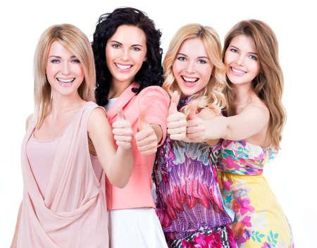 白い背景の上にスタジオでポーズをとってサインを親指で若い美しい幸せな女性のグループ。