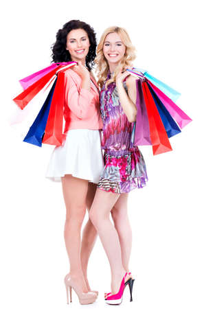 woman bag: Two attractive smiling woman with multicolor shopping bags standing on a white background. Stock Photo