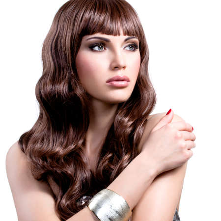 is long: Portrait of a beautiful young woman with long brown hairs. Pretty girl model with stylish bijouterie of silver color.