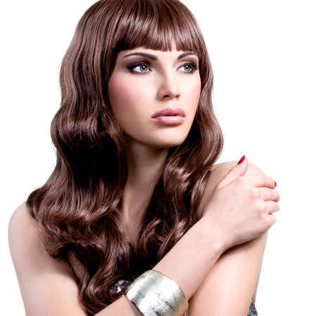 pelo largo: Retrato de una mujer joven hermosa con los pelos marrones largos. Modelo de la muchacha bonita con bisutería elegante de color plateado. Foto de archivo