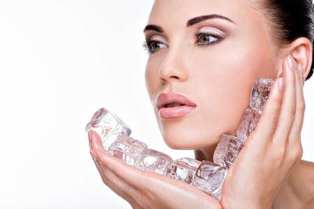 caras: Mujer joven hermosa que aplica el hielo a cara. Concepto de cuidado de la piel.