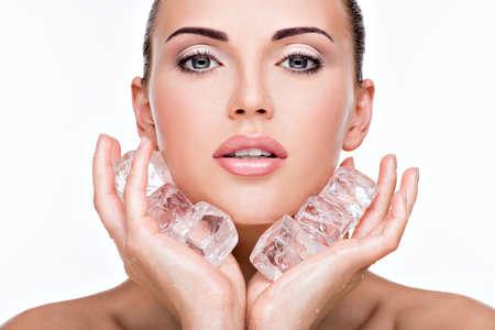 Belle jeune femme applique la glace à face. Concept de soins de la peau.