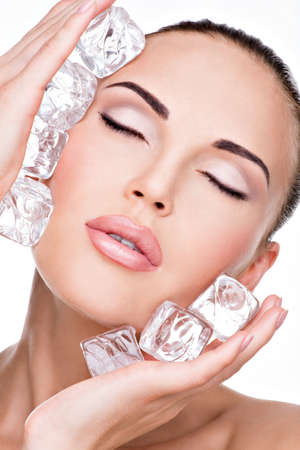 beauty eyes: Beautiful young woman applies the ice to face. Skin care concept.