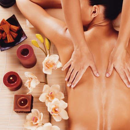 Masér dělá masáž na ženu zpět v lázeňském salonu LANG_EVOIMAGES