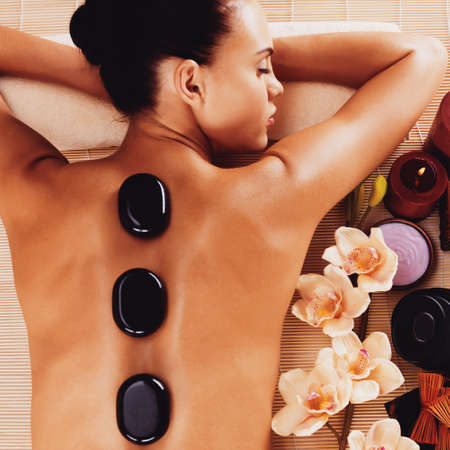 vertical wellness: Adult woman relaxing in spa salon with hot stones on body. Beauty treatment therapy
