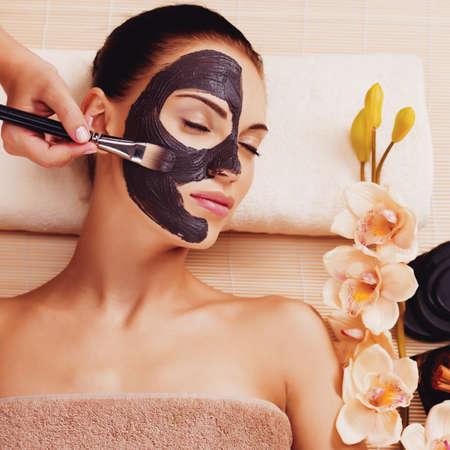 masaje facial: Frotis Cosmetologist máscara de cosméticos en la cara de la mujer en el salón de la savia