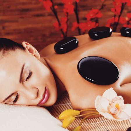 hot stones: Adult woman relaxing in spa salon with hot stones on back. Beauty treatment therapy LANG_EVOIMAGES