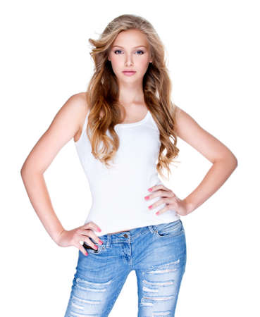 Beautiful young sexy woman with long curly hair in blue jeans posing in studio over white background.