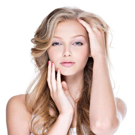 白で隔離 - 彼女の顔に触れる長い巻き毛の美しい若い女性の肖像画。