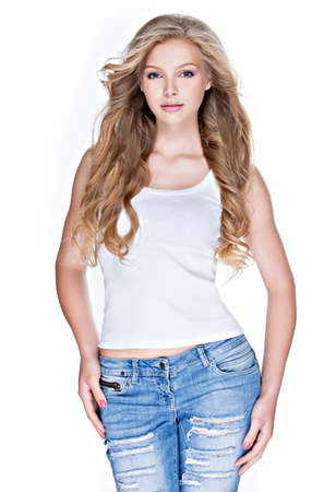 portrait studio: Beautiful young sexy woman with long curly hair in blue jeans posing in studio over white background.