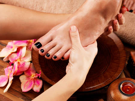 Massage of womans foot in spa salon - Beauty treatment concept
