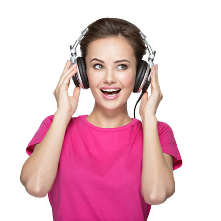 auriculares: Alegre escuchando música mujer joven con auriculares en el fondo blanco