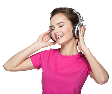 listening: Cheerful young woman listening music with headphones on white background LANG_EVOIMAGES