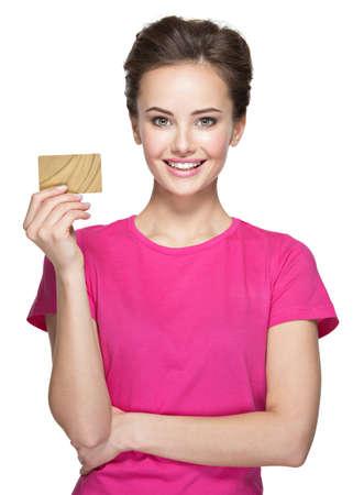 De jonge glimlachende vrouw houdt een creditcard op wit wordt geïsoleerd
