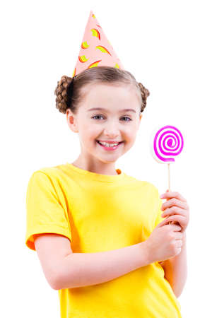 hubcap: Happy little girl in yellow t-shirt and party hat holding colored candy - isolated on white.