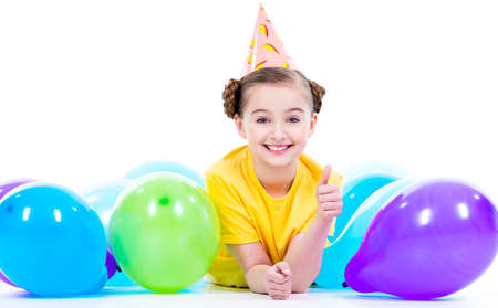 children birthday: Happy smiling girl in yellow t-shirt lying on the floor with colorful balloons and showing thumbs up - isolated on a white.
