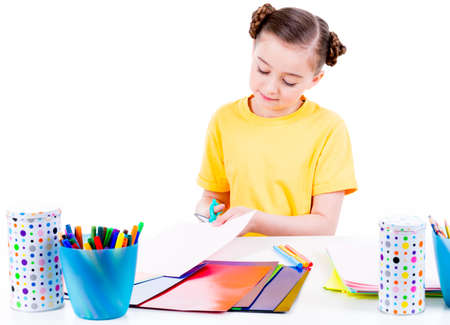arts: Portrait of cute little girl in yellow t-shirt cut scissor cardboard - isolated on white. Stock Photo