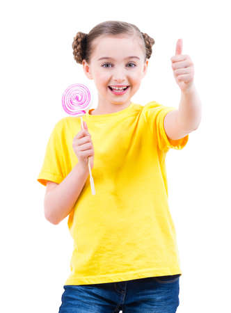 yellow shirt: Happy pretty girl in yellow t-shirt with colored candy showing thumbs up sign - isolated on white. Stock Photo