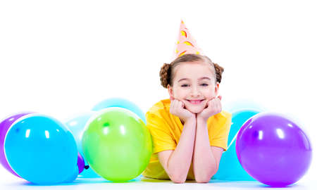 hubcap: Happy smiling girl in yellow t-shirt  lying on the floor with colorful balloons - isolated on a white.