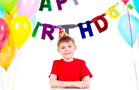 hubcap: Happy little boy sitting at the table having fun in a birthday party - isolated on a white.