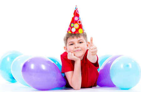 hubcap: Happy smiling boy in red t-shirt lying on the floor with colorful balloons and showing thumbs up - isolated on a white.