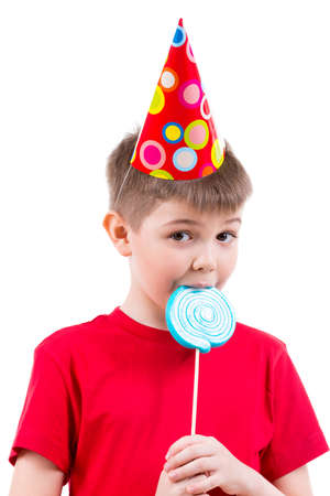 red tshirt: Young boy in red t-shirt and party hat eating colored candy - isolated on white.