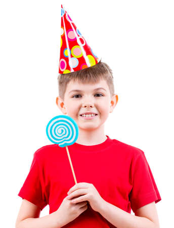 hubcap: Smiling boy in red t-shirt and party hat holding colored candy - isolated on white.